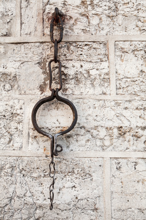 Medieval shackles mounted in old stone wall on Town Hall square in old Tallinn, Estonia