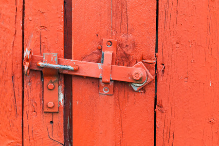 Old metal latch on red wooden door, close-up photo