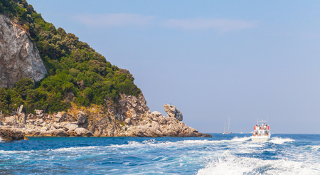 Small touristic motorboat goes near rocks of Capri island, Italy