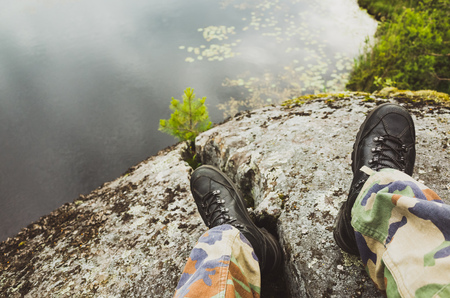 uniform green shoe: Male feet in camouflage pants and black rough shoes. Travel lifestyle background. Vintage tonal correction photo filter, old style Stock Photo