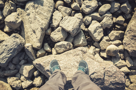tonal: Male feet in blue canvas sport shoes standing on coastal rough rocky ground. Travel lifstyle background. Vintage warm tonal correction photo filter, old style effect
