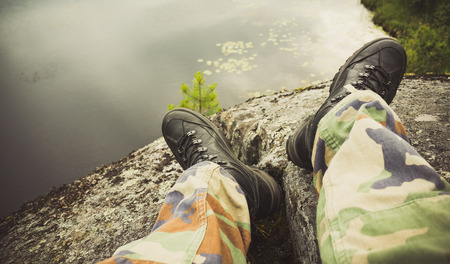 Male feet in camouflage pants and black rough shoes. Travel lifestyle background. Vintage tonal correction photo filter, old style effect