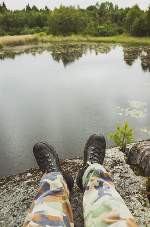 uniform green shoe: Male feet in camouflage pants and black rough shoes. Vertical travel lifestyle background. Vintage tonal correction photo filter, old style effect