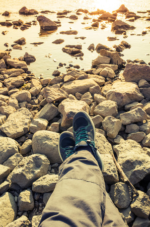 tonal: Male feet in blue canvas sport shoes standing on coastal rough rocky ground. Vertical travel lifstyle background. Vintage warm tonal correction photo filter, old style effect