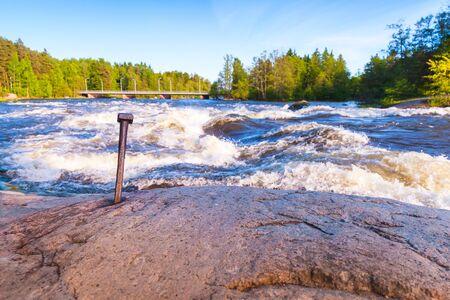 Langinkoski, fast running river water and coastal stones. Kotka, Finland. Black and white natural photo Stock Photo