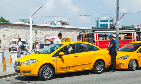 Istanbul, Turkey - July 1, 2016: Taxi drivers and passengers near yellow cars on Taksim square. Cityscape of Istanbul city