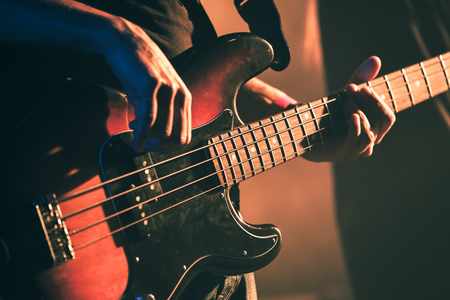 Closeup vintage toned photo of bass guitar player hands, soft selective focus, live music theme, old style filter effect