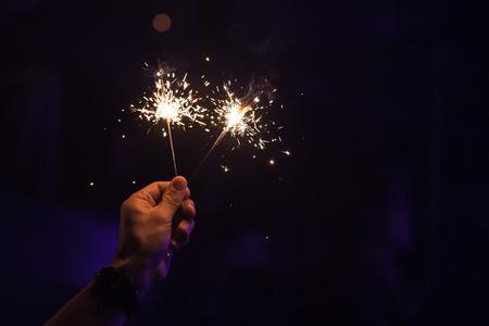 Twee sterretjes branden in één mannelijke hand over donkere nachtachtergrond, zachte selectieve nadruk Stockfoto