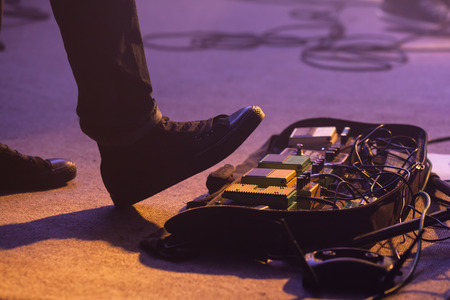 Electric bass guitar player on a stage with set of distortion effect pedals under his foot. Selective focus