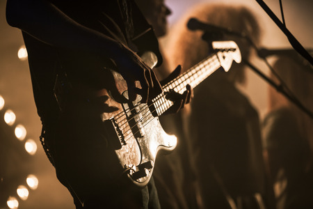 strobe: Electric bass guitar player on the stage with strobe illumination, live hard rock music theme Stock Photo