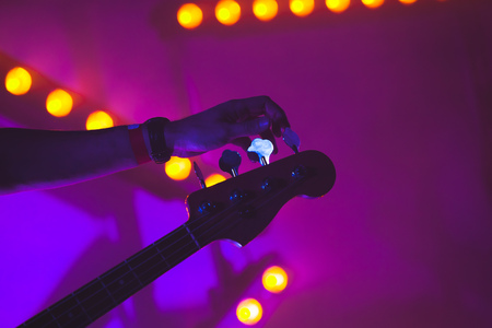 Live music background, guitarist tunes electric bass guitar, closeup photo with soft selective focus and colorful illumination