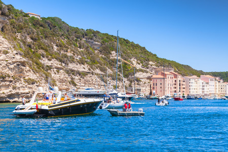 Bonifacio, France - July 2, 2015: Pleasure yacht with ordinary tourists enters the port  of Bonifacio, small resort port city of Corsica island in summer sunny day, mooring service staff in work