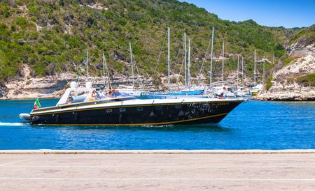 Bonifacio, France - July 2, 2015: Luxury pleasure boat with ordinary tourists enters the port  of Bonifacio, small resort port city of Corsica island in sunny summer day