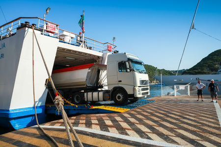 Bonifacio, France - July 3, 2015: Cargo truck leaves out the ferry in port of Bonifacio, small resort port city of Corsica island in sunny summer day, people from port staff lead the action