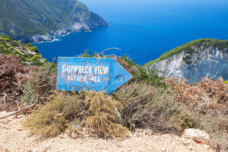 ship wreck: Zakynthos, Greece - August 20, 2016: Old blue wooden sign shows direction to Ship Wreck viewpoint, Navagio bay, Greece. The most popular natural landmark of Zakynthos, Greek island in the Ionian Sea Editorial