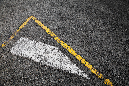 one lane road sign: Road marking, white stripe and corner of yellow borders line over black asphalt pavement, background photo Stock Photo
