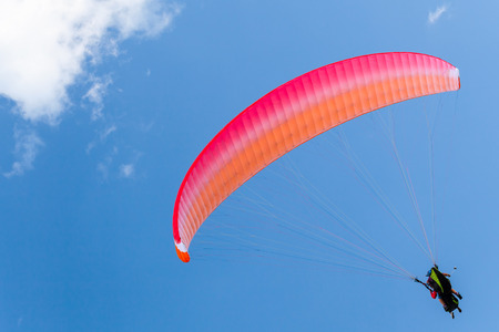Paragliders in blue sky with clouds, tandem of instructor and beginner under red parachute Stock Photo