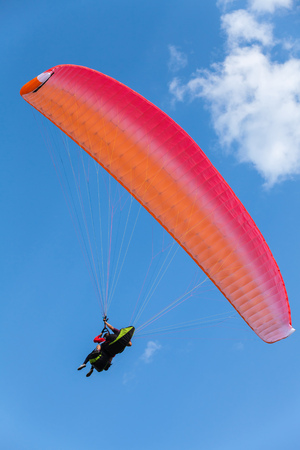 Paragliding in blue sky with clouds, tandem of instructor and beginner under red parachute, vertical photo Stock Photo