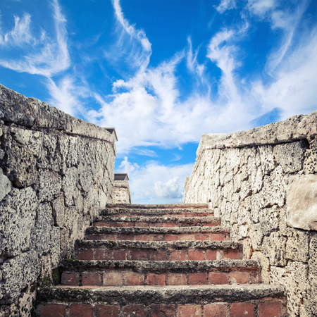 Ancient stone stairway goes up under blue cloudy sky background
