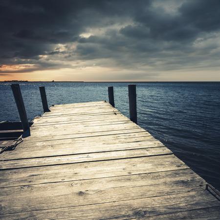 Empty wooden pier perspective under dark dramatic stormy clouds