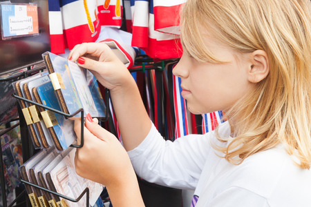 Paris, France - August 11, 2014: Blond Caucasian girl considers souvenirs in small street gift shop Editorial