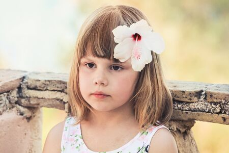 Serious Caucasian little girl with white flower in hair, close-up outdoor portrait, photo with old style tonal correction filter effect