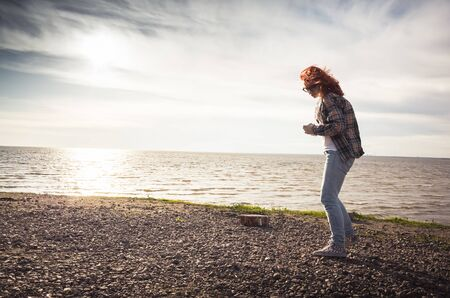 Girl walking on a sea coast, vintage tonal correction photo filter effect