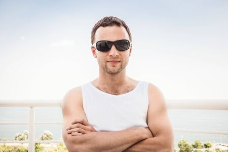 stands: Young adult sporty Caucasian man in white shirt and black sunglasses stands with crossing hands. Outdoor summer portrait with sea on a background Stock Photo
