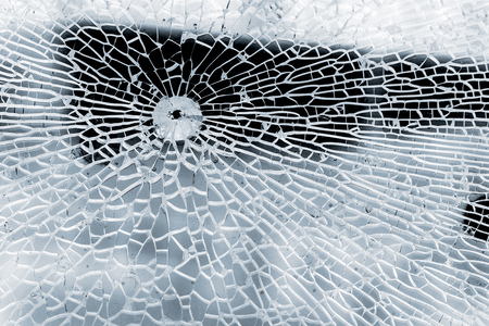 strained: Broken strained glass with bullet hole and craks. Close-up background photo texture
