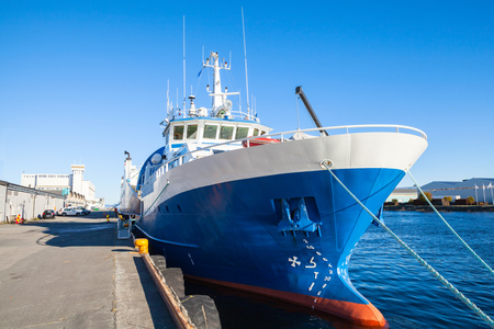 ship bow: Blue and white industrial cargo ship stands moored in port of Trondheim, Norway