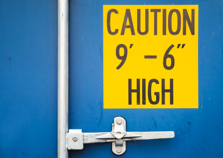 standard steel: Caution high yellow sign on closed gate of standard blue cargo shipping container Stock Photo