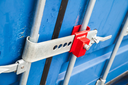 standard steel: Red lock on the gate of standard blue cargo container for shipping transportation