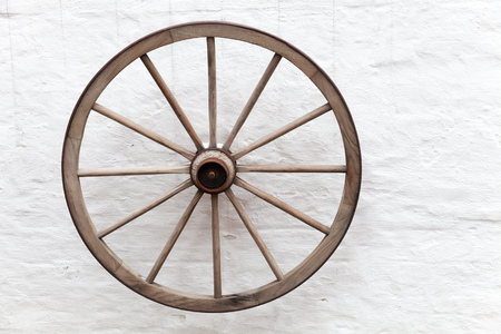 Old wooden cart wheel hanging on white rural wall