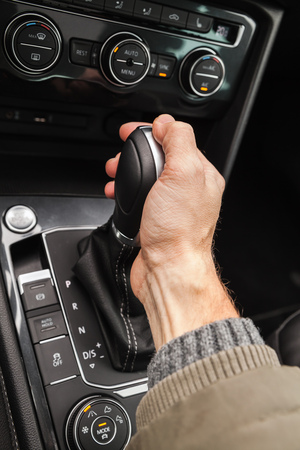 reverse: Driver hand holds gear lever of modern luxury crossover car. Close-up photo with selective focus