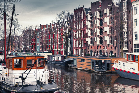 Colorful traditional living houses and houseboats along the canal in Amsterdam, Netherlands. Cold vintage tonal correction filter effect Editorial