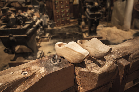 klompen: Pair of clogs made of poplar wood. Klompen, traditional Dutch shoes for everyday use stand on wooden beam in manufacturing facility Stock Photo