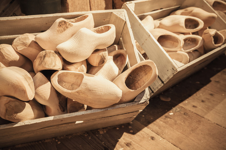 klompen: Clogs made of poplar wood. Klompen, traditional Dutch shoes for everyday use lay in wooden boxes Stock Photo