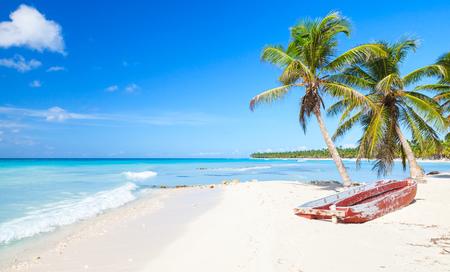 Coconut palms and old red pleasure boat are on white sandy beach. Caribbean Sea, Dominican republic, Saona island coast, popular touristic resort Banco de Imagens