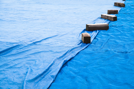 waterproofing material: Blue industrial mesh textile with wooben planks covers ground area under construction
