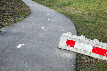 Concrete road block with red white striped warning sign lays on the roadside Stock Photo