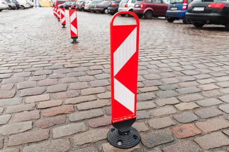 Vertical red and white striped caution road signs stand in a row to divide a parking lot area