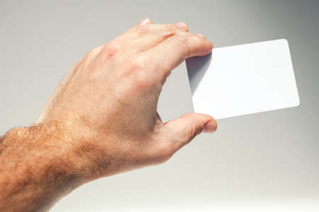keycard: Male hand holds white empty card over gray background, close up photo