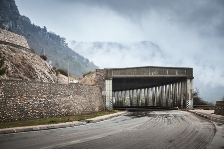 Mountain road with concrete tunnel structure in foggy rainy day, rural auto travel theme