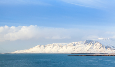 Coastal Icelandic landscape with snowy mountains under blue cloudy sky. Reykjavik distict, Iceland