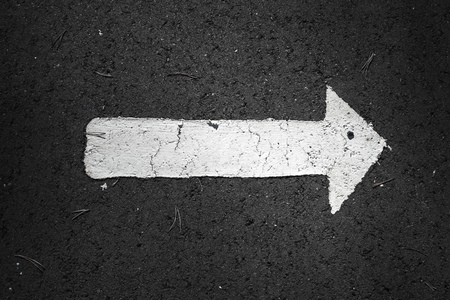 one lane sign: White arrow over black highway asphalt, right drive direction Stock Photo