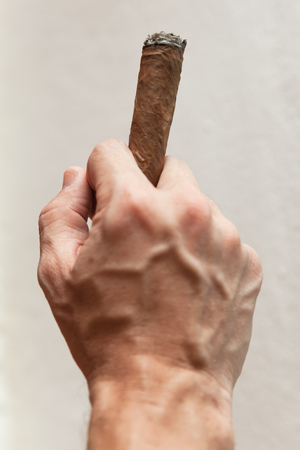 Gesture with handmade cigar in male hand, close-up photo with selective focus over white wall background