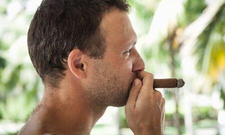 Young European man smokes handmade cigar; closeup profile portrait with selective focus. dominican Republic Stock Photo