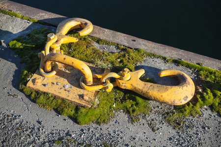 Ships mooring equipment, yellow hooks for ropes mounted in concrete pier