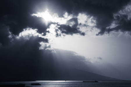 Dramatic sky with clouds and sunlight rays over sea. Blue toned photo filter effect Reklamní fotografie