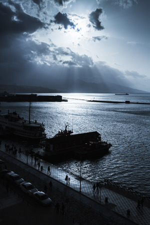 Dark dramatic sky with clouds and sunlight rays over sea. Port of Izmir. Blue toned photo filter effect Reklamní fotografie